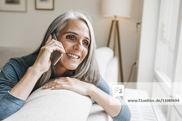 Lächelnde Frau sitzt auf der Couch und telefoniert mit dem Handy.