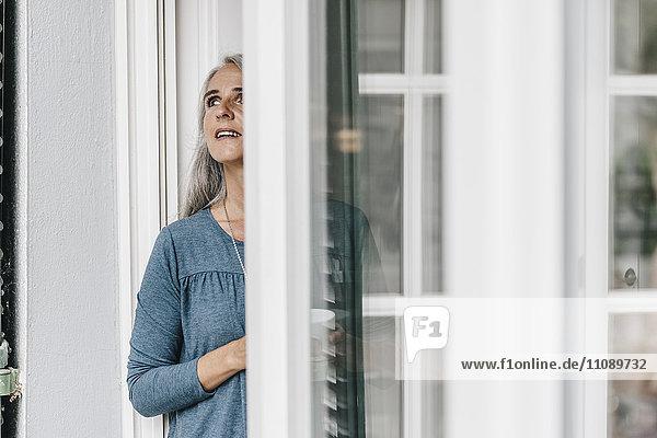 Frau steht vor offener Terrassentür und schaut nach oben.