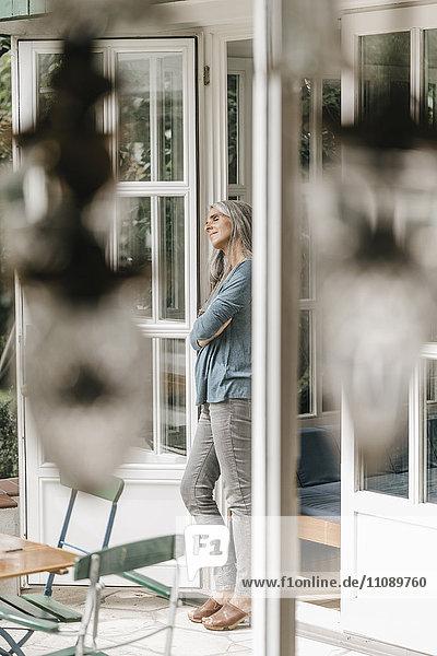 Frau lehnt am Türrahmen ihres Wintergartens
