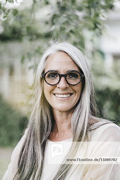 Porträt einer lächelnden Frau mit langen grauen Haaren und Brille