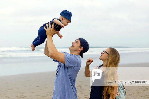 Indonesien  Bali  Glückliche Eltern mit Baby am Strand