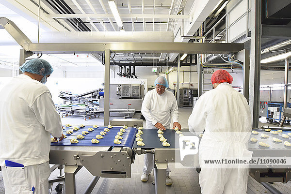 Arbeiter an der Produktionslinie einer Backfabrik mit Croissants