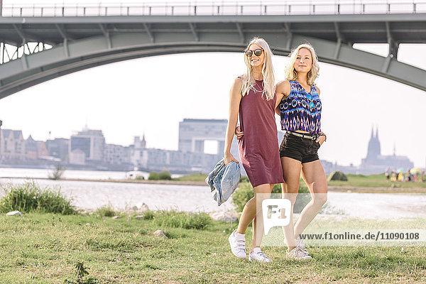 Zwei lächelnde junge Frauen  die am Flussufer spazieren gehen.