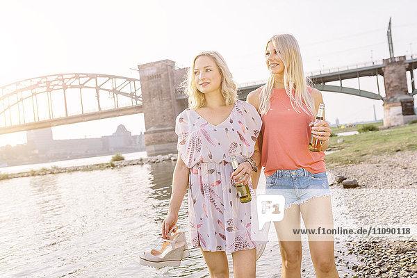 Zwei junge Frauen mit Bierflaschen am Flussufer