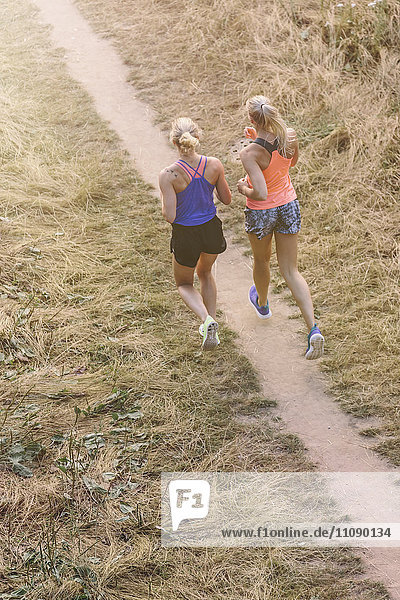 Two young women running on field path