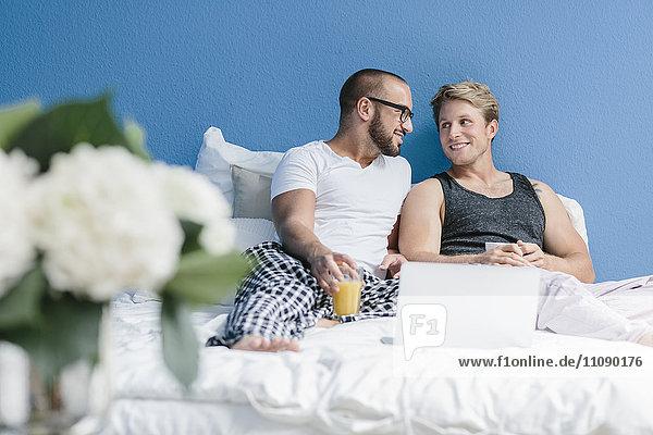 Schwules Paar im Bett liegend  mit Laptop