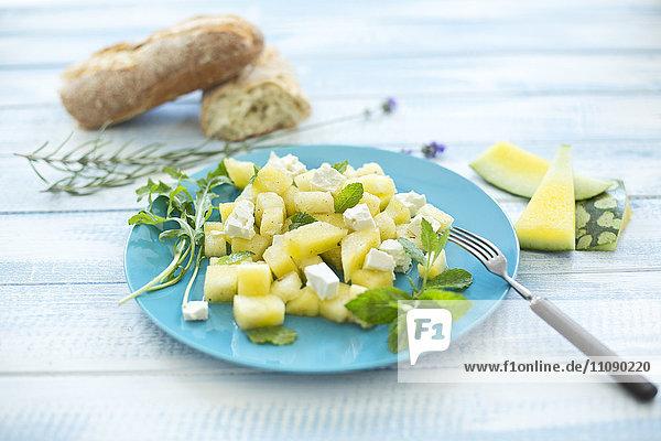 Melonensalat  gelbe Wassermelone  Feta  Minze und Rucola auf dem Teller
