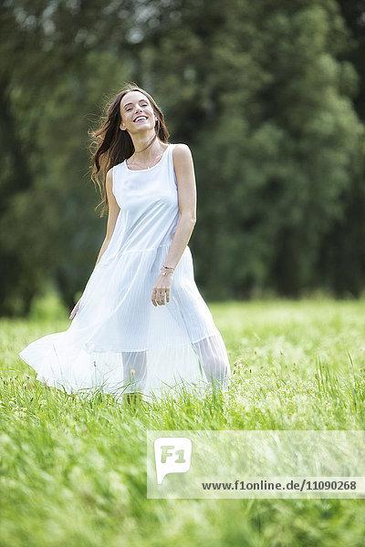 Glückliche Frau in weißem Sommerkleid stehend auf einer Wiese