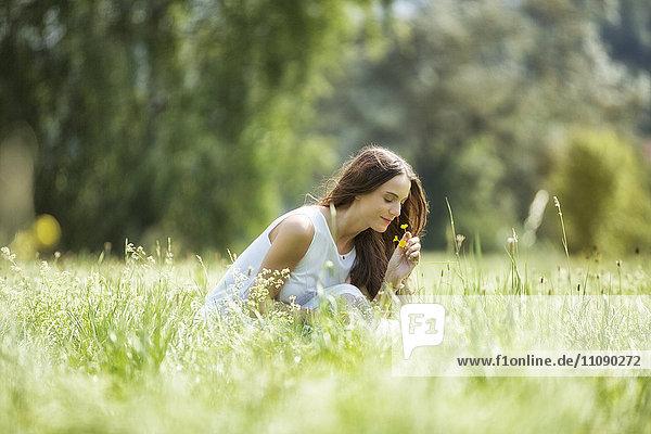 Frau hockt auf einer Wiese und riecht nach Blumen.