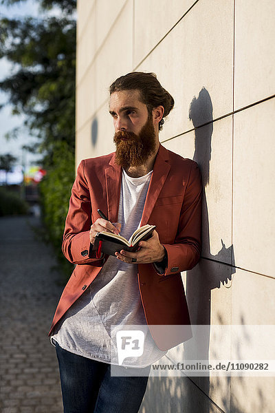 Fashionable young man with notebook leaning against wall looking at distance