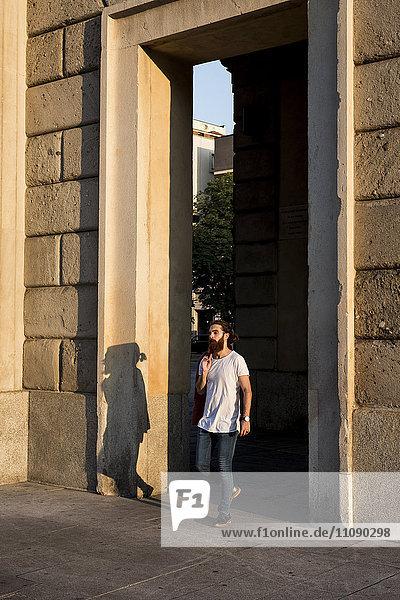 Junger Mann  der in der Stadt spazieren geht.