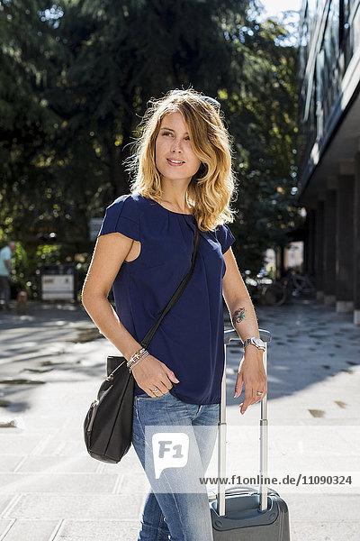 Porträt eines blonden Touristen mit Gepäck