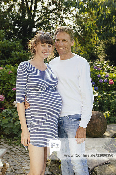 Happy couple with pregnant woman standing in garden