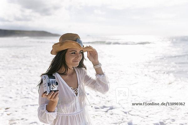 Asturien  Spanien  schöne junge Frau mit Kamera am Strand