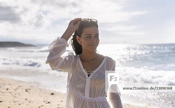 Schöne junge Frau am Strand bei Sonnenuntergang