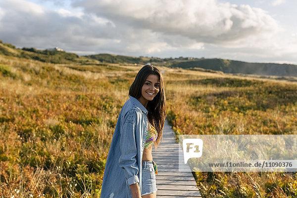 Spanien  Asturien  schöne junge Frau an der Strandpromenade am Abend