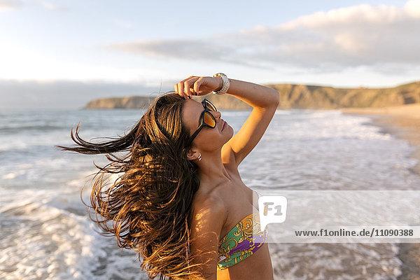 Spanien  Asturien  schöne junge Frau am Strand bei Sonnenuntergang