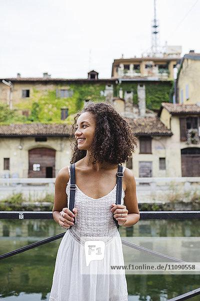 Italien  Mailand  lächelnde junge Frau mit Rucksack in weißem Sommerkleid vor dem Wasser stehend