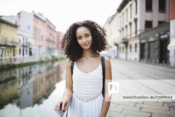 Italien  Mailand  Porträt einer lächelnden jungen Frau mit lockigem braunem Haar