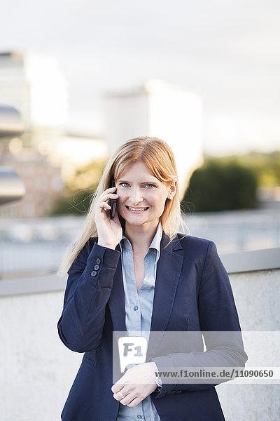 Porträt einer lächelnden blonden Geschäftsfrau am Telefon
