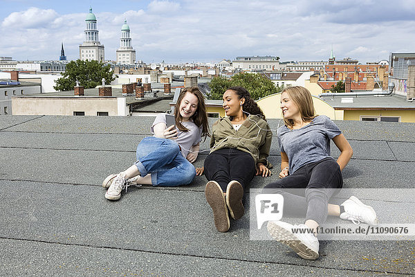 Germany  Berlin  three teenage girls sitting on roof top listening music with earphones