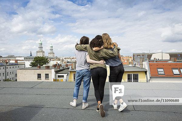 Deutschland  Berlin  Rückansicht von drei Teenagern  die Arm in Arm auf dem Dach stehen.