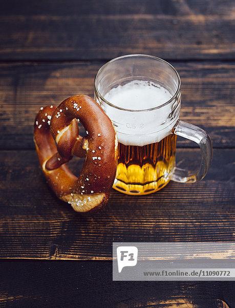 Brezel und Glas Bier auf dunklem Holz