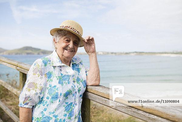 Glückliche Seniorin mit Strohhut auf der Promenade stehend