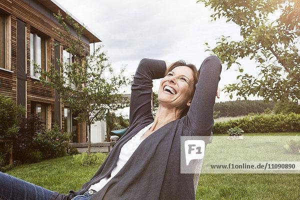 Lachende Frau entspannt im Garten