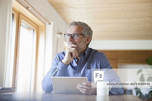 Erwachsener Mann mit digitalem Tablett auf dem Tisch zu Hause