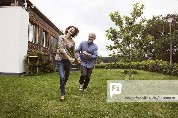Ein glückliches reifes Paar  das im Garten läuft
