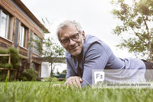 Porträt eines lächelnden reifen Mannes im Garten liegend