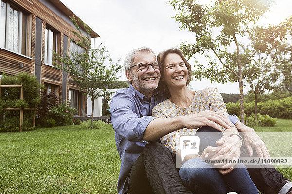 Glückliches reifes Paar im Garten sitzend