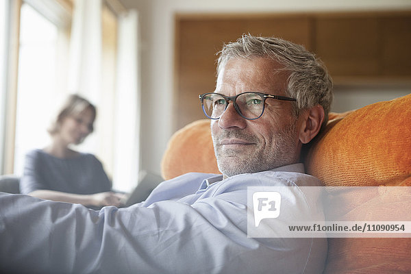 Mann entspannt im Sessel mit Frau im Hintergrund