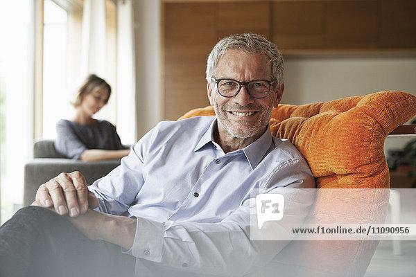 Lächelnder Mann entspannt im Sessel mit Frau im Hintergrund