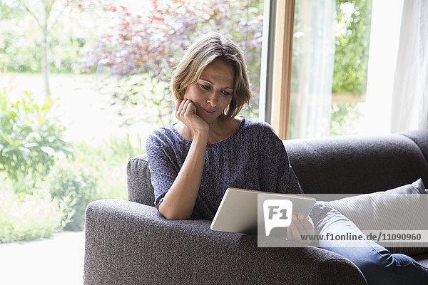 Frau mit digitalem Tablett auf der Couch