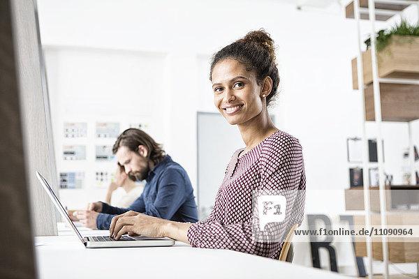 Lächelnde Frau im Büro bei der Arbeit am Laptop