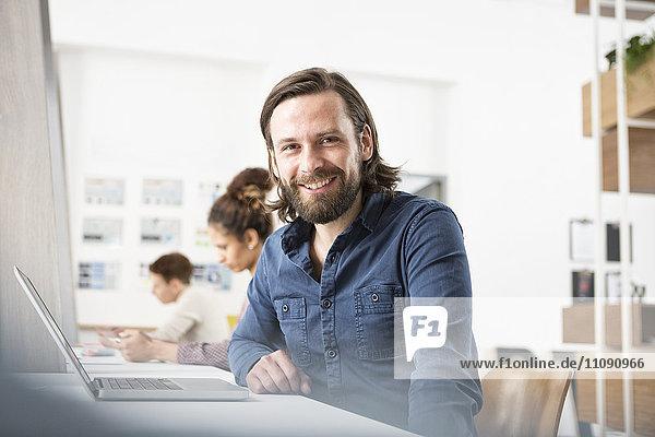 Lächelnder Mann im Büro mit Laptop