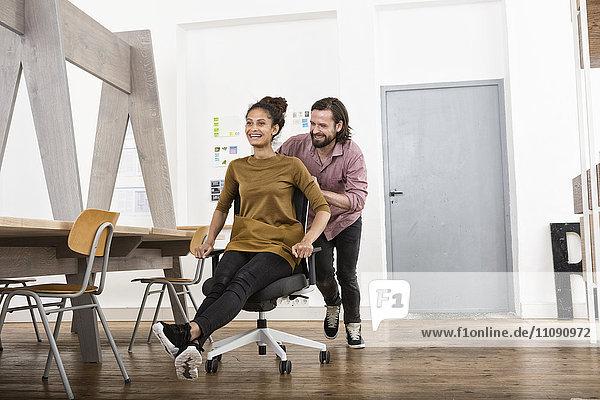 Mann schiebt glückliche Frau auf Bürostuhl