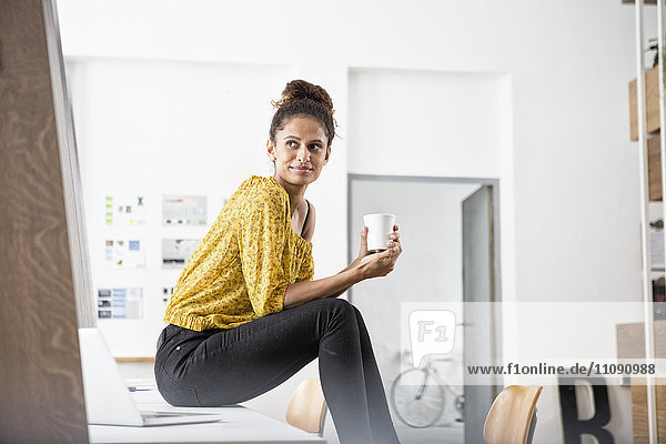 Smiling woman sitting on office desk holding cup