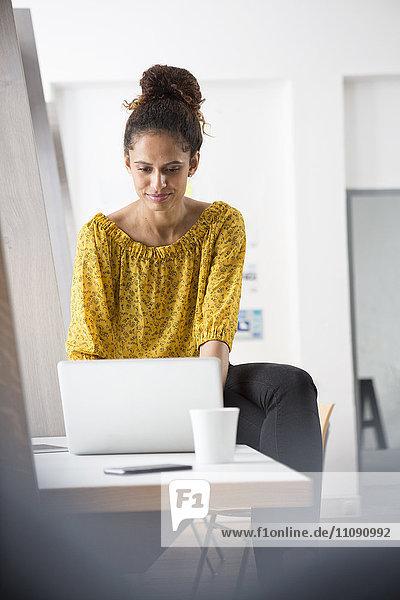 Lächelnde Frau auf dem Schreibtisch sitzend mit Laptop