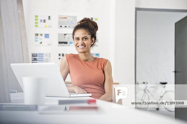 Lächelnde Frau sitzt am Schreibtisch mit Laptop