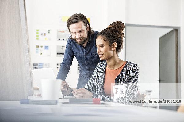 Zwei Kollegen arbeiten zusammen am Schreibtisch