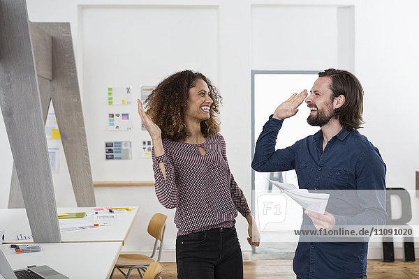 Zwei glückliche Kollegen im Büro High Fiving