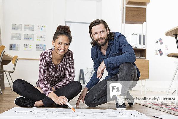 Porträt von zwei lächelnden Kollegen im Bürogeschoss mit Bauplan