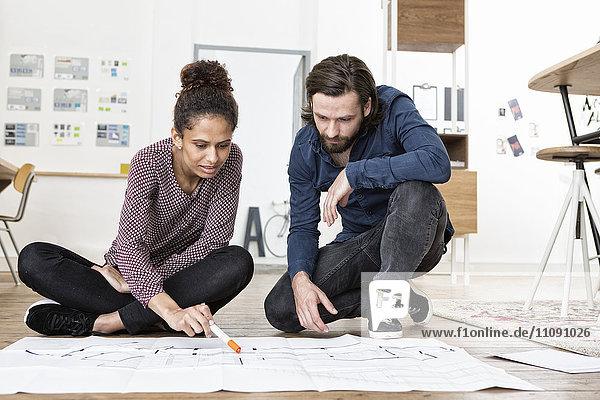 Two colleagues on office floor looking at construction plan