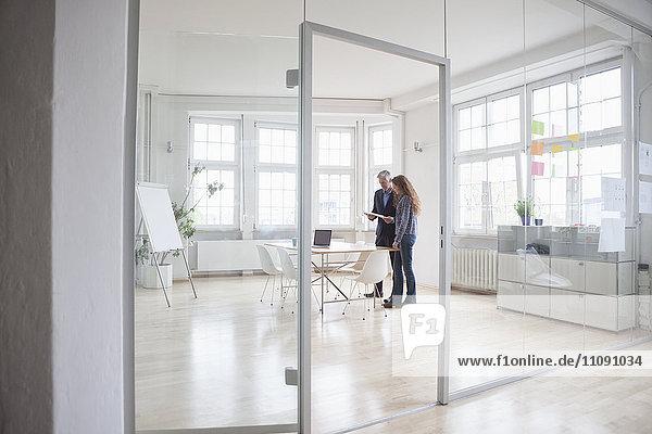 Geschäftsmann und Frau stehen in einem hellen Büro