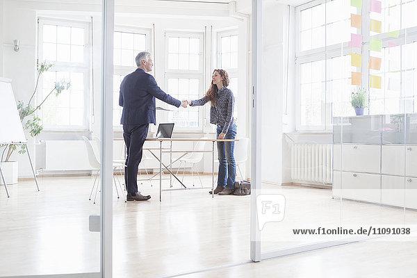 Geschäftsmann und Frau beim Händeschütteln im hellen Büro