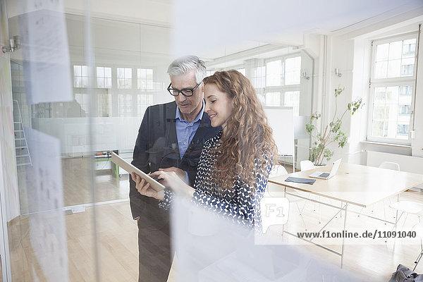 Geschäftsmann und Frau mit digitalem Tablett im Büro