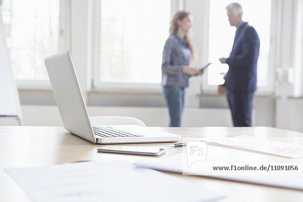 Laptop und Dokumente auf dem Schreibtisch mit Geschäftsleuten im Hintergrund